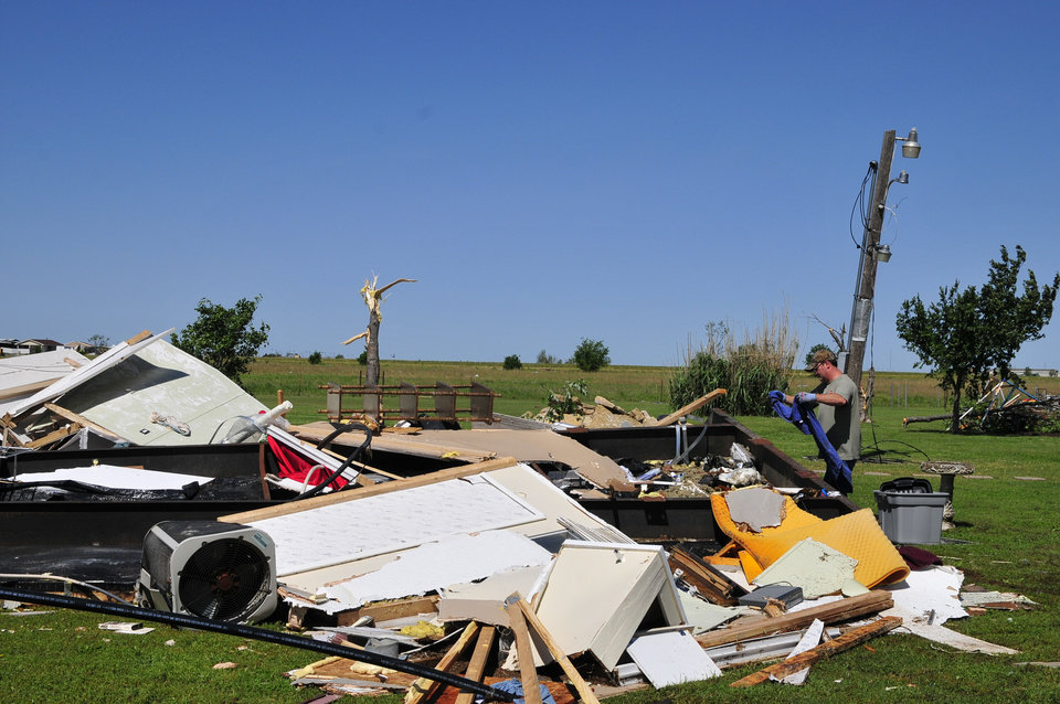 Photo - An El Reno, Okla. resident searches through the wreckage of a friend's mobile home hoping to find undamaged belongings in El Reno on Saturday June 1, 2013. (AP Photo/Nick Oxford)