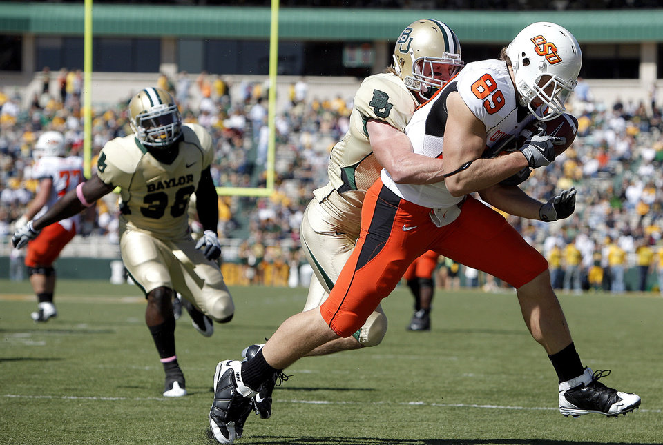 Photo - OSU's Cooper Bassett (89) scores a touchdown as he is brought down by Baylor's Jordan Lake (21) during the college football game between Baylor University and Oklahoma State University (OSU) at Floyd Casey Stadium in Waco, Texas, Saturday, Oct. 24, 2009.  Photo by Sarah Phipps, The Oklahoman