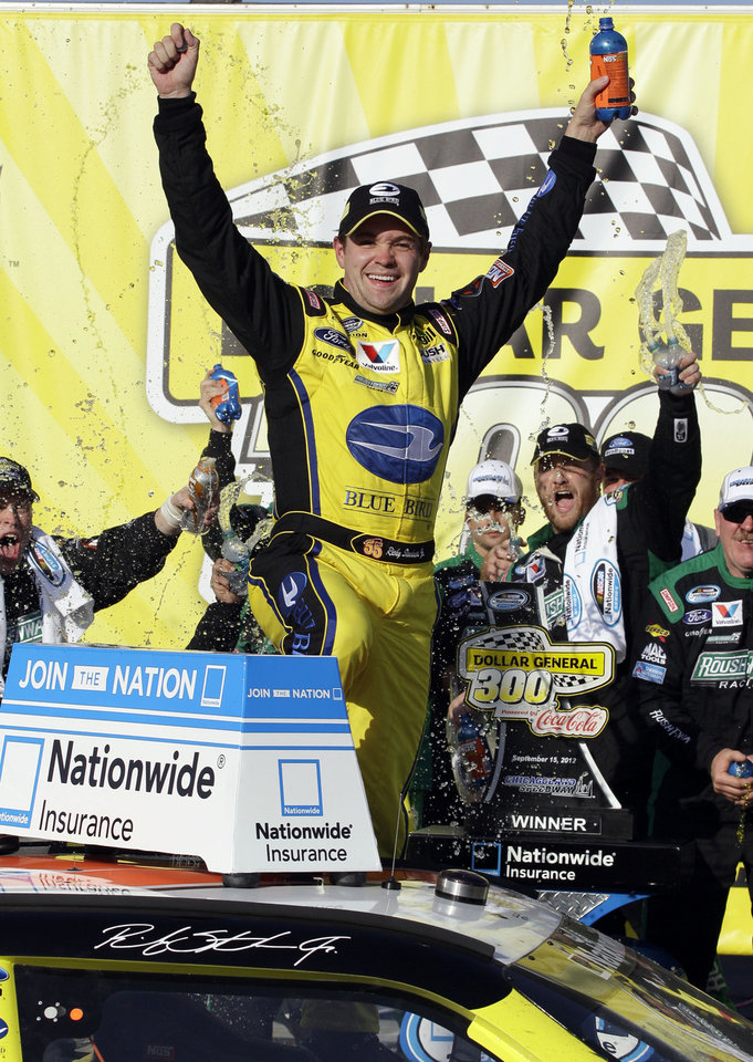 Photo -   Ricky Stenhouse Jr., celebrates his victory with his crew members in victory lane after winning the NASCAR Nationwide Series Dollar General 300 auto race at Chicagoland Speedway in Joliet, Ill., Saturday, Sept. 15, 2012. (AP Photo/Nam Y. Huh)