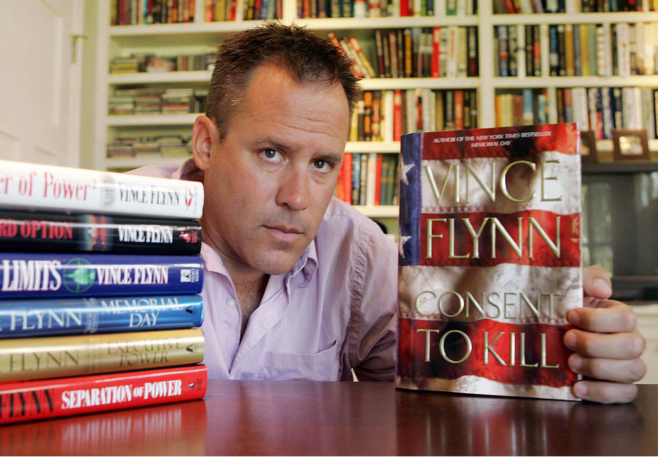 "FILE - In a Sept. 2, 2005 file photo, best-selling author Vince Flynn poses with the dust jacket of his new book, ""Consent to Kill,"" and copies of his six other books in his home in Edina, Minn. Flynn died, Wednesday, June 18, 2013, after a two-year battle with prostate cancer, a statement from Flynn's publisher, Simon & Schuster, Inc., said. He was 47. (AP Photo/Jim Mone, File)"