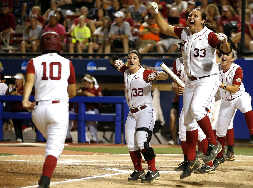 Photo - Alabama's Jaclyn Traina, right, and Ryan Iamurri celebrate afte Alabama hit a three-run home run in the fourth inning of a Women's College World Series game between at ASA Hall of Fame Stadium in Oklahoma City Thursday, May 29, 2014. Photo by Bryan Terry, The Oklahoman