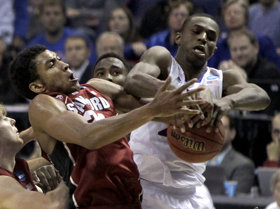 Photo - Kansas' Andrew Wiggins, right, and Stanford's Josh Huestis reach for a rebound during the first half of a third-round game of the NCAA college basketball tournament Sunday, March 23, 2014, in St. Louis. (AP Photo/Jeff Roberson)