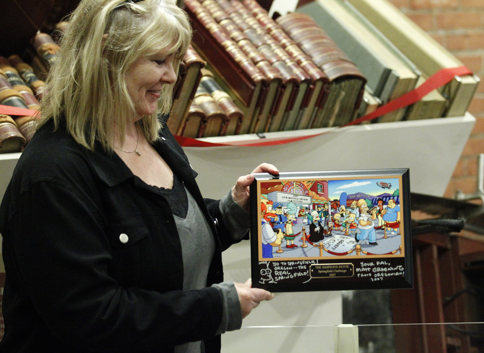 Photo -   Debra Gruell, Executive Director Springfield Museum, holds a plaque that was given by