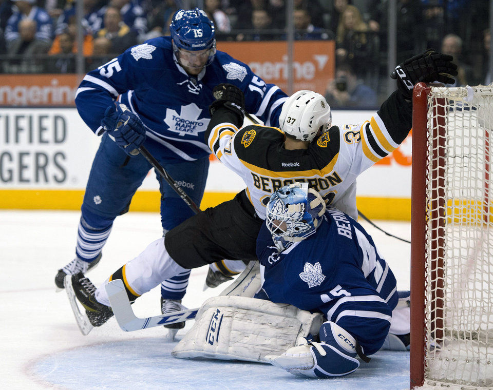 Photo - Toronto Maple Leafs defenseman Paul Ranger (15) drives Boston Bruins center Patrice Bergeron onto goaltender Jonathan Bernier during the third period of an NHL hockey game in Toronto on Thursday, April 3, 2014. Bernier left the game injured on the play. (AP Photo/The Canadian Press, Frank Gunn)