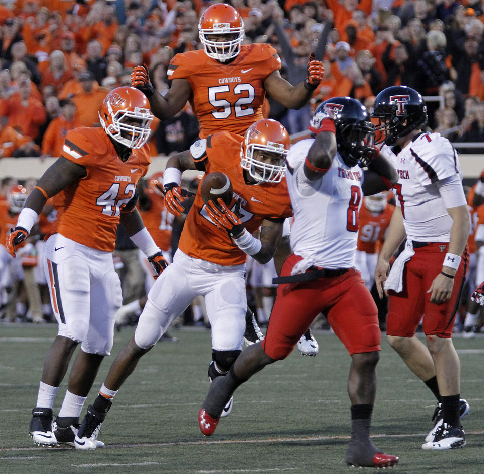 Photo - Oklahoma State's Lyndell Johnson (27) reacts with Ryan Simmons (52) and DeMarcus Sherod (42) after recovering a fumble by Texas Tech during the college football game between the Oklahoma State University Cowboys (OSU) and Texas Tech University Red Raiders (TTU) at Boone Pickens Stadium on Saturday, Nov. 17, 2012, in Stillwater, Okla.   Photo by Chris Landsberger, The Oklahoman