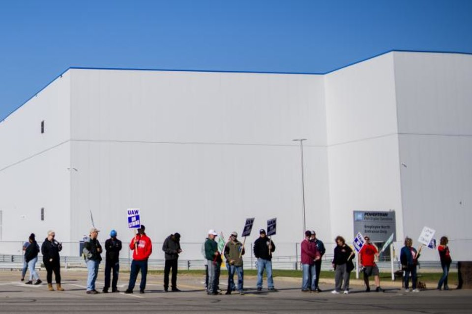 Photo -  General Motors' Flint Assembly Plant employees line the street with picket signs during the nationwide UAW strike against General Motors on Monday. [AP PHOTO]