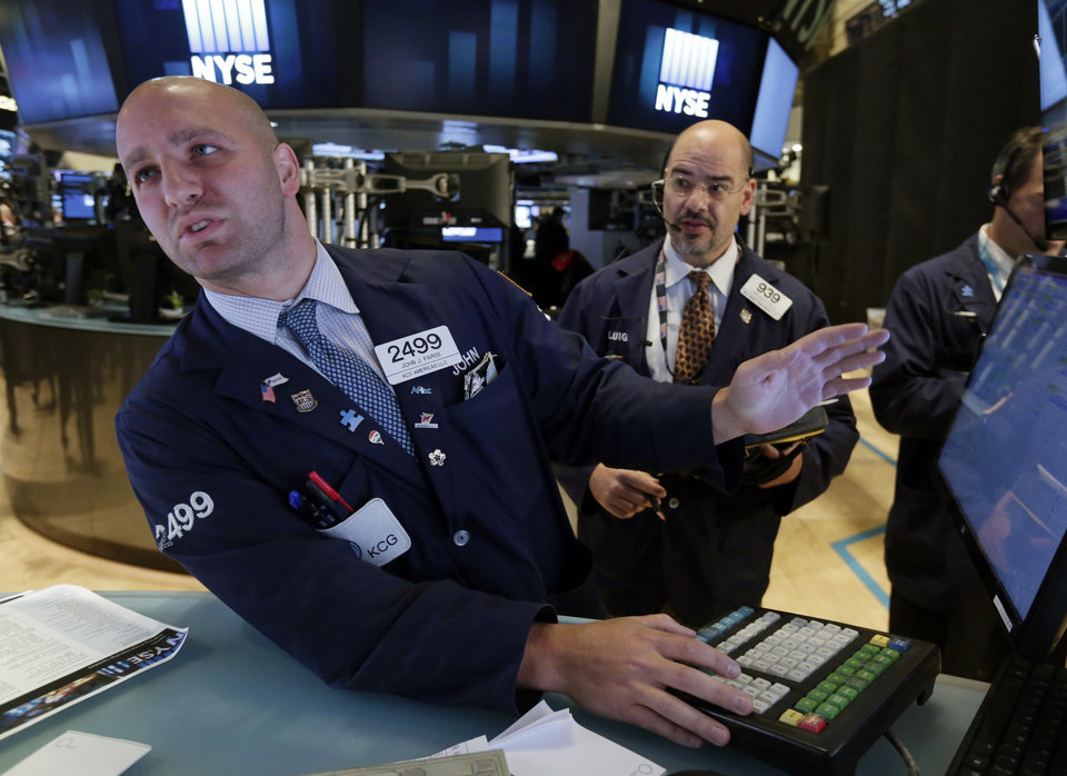 Photo - Specialist John Parisi, left, and trader Luigi Muccitelli work on the floor of the New York Stock Exchange, Tuesday, Aug. 5, 2014. U.S. stock prices are opening lower as traders digest some mixed corporate earnings and a weak indicator on the Chinese economy. (AP Photo/Richard Drew)
