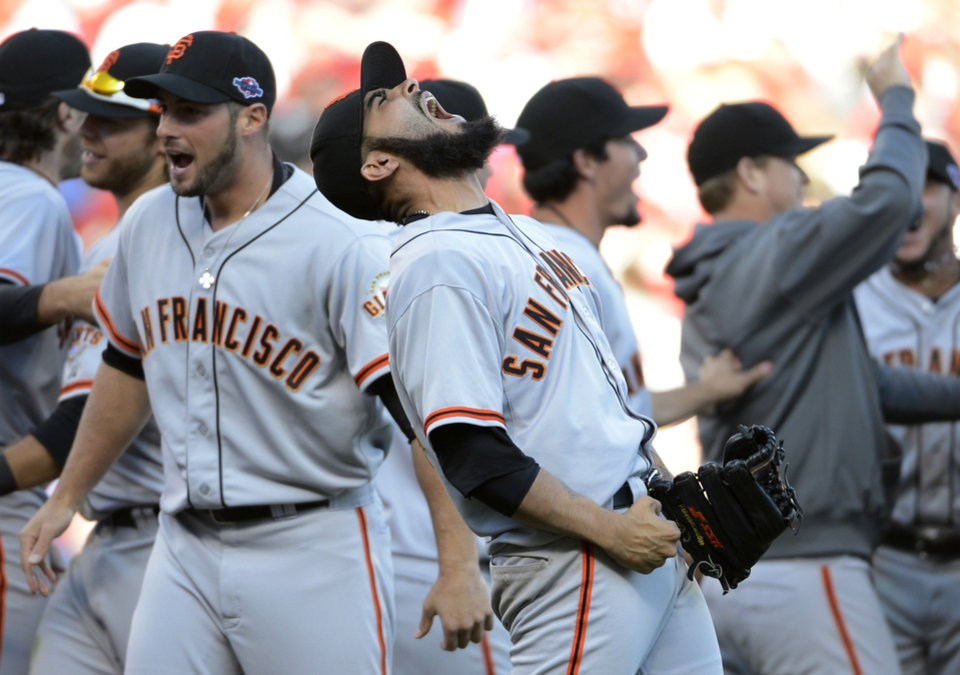 Photo -   San Francisco Giants relief pitcher Sergio Romo, center, celebrates with teammate after the Giants defeated the Cincinnati Reds 6-4 in Game 5 of the National League division baseball series, Thursday, Oct. 11, 2012, in Cincinnati. The Giants won the final three games, all in Cincinnati, and advanced to the NL championship series. (AP Photo/Michael Keating)