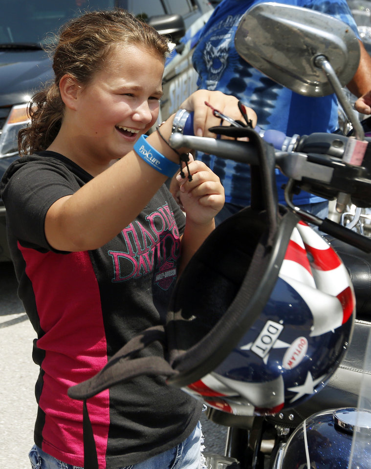 Photo -  Katie McGann reacts to the sound of the engine as she revs a Harley-Davidson motorcycle. [Photo by Nate Billings, The Oklahoman]