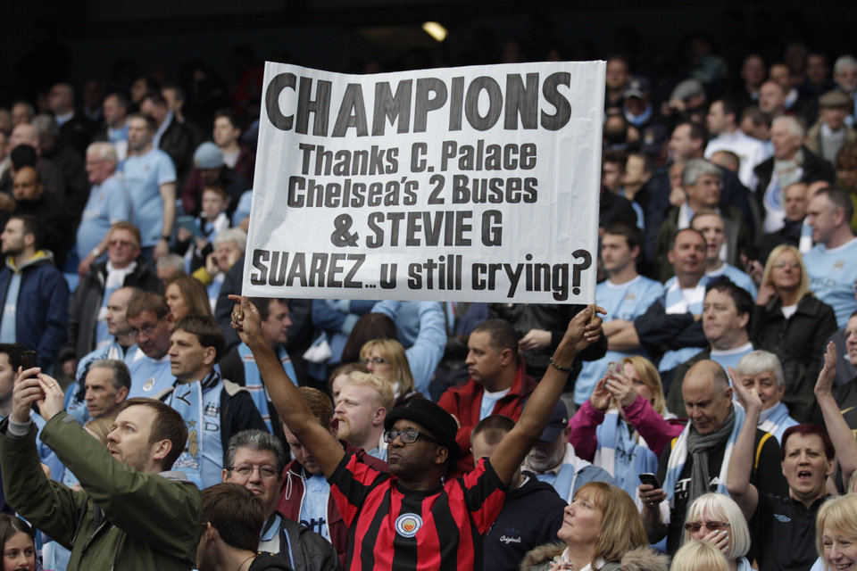 Photo - A Manchester City fan holds up a placard during the English Premier League soccer match between Manchester City and West Ham at the Etihad Stadium in Manchester, England, Sunday May 11, 2014.  Manchester City won the Premier League for the second time in three seasons on Sunday, completing its campaign with a comfortable 2-0 victory over West Ham that lacked any of the drama of its previous title.  (AP Photo/Jon Super)