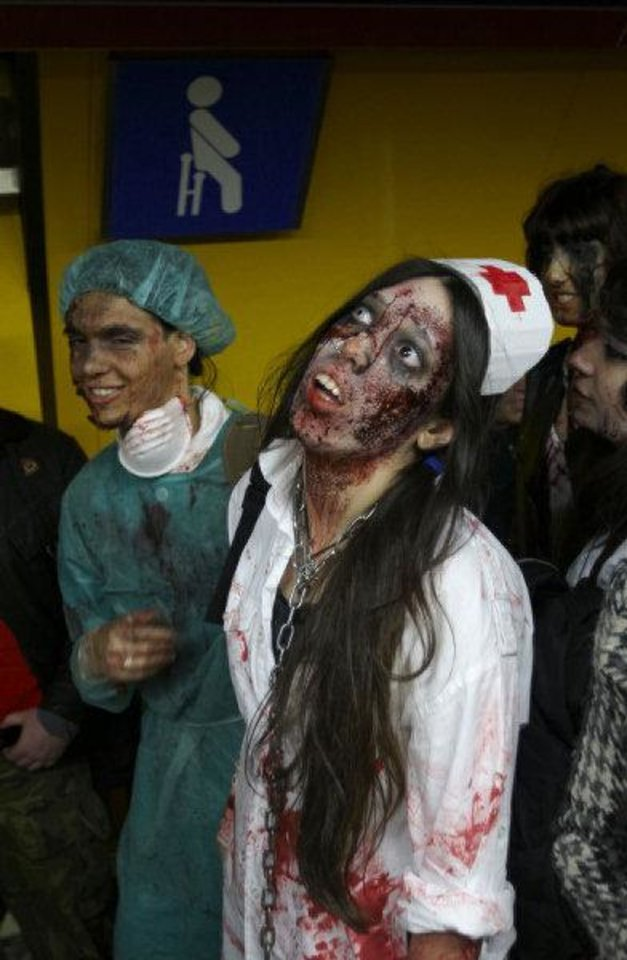 Photo - People dressed and made up as Zombies wait on the platform for a metro train during the annual Zombie march in Madrid, Saturday Feb. 27, 2010. The zombie march is in homage by fans to the Zombie film genre and to U.S. director George A. Romero, famous for his Zombie horror movies. (AP Photo/Paul White)