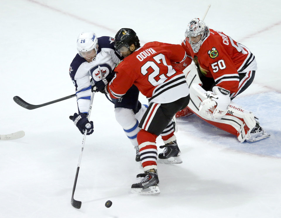 Photo - Chicago Blackhawks defenseman Johnny Oduya (27) keeps Winnipeg Jets right wing Blake Wheeler (26) away from a loose puck as goalie Corey Crawford defends during the first period of an NHL hockey game, Sunday, Jan. 26, 2014, in Chicago. (AP Photo/Charles Rex Arbogast)