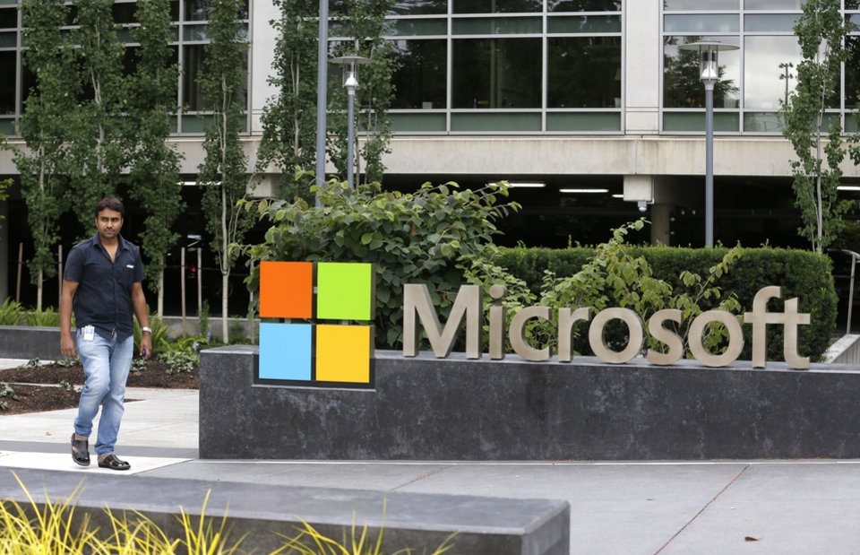 Photo - In this photo taken July 3, 2014, a worker walks past a Microsoft Corp. sign outside the Microsoft Visitor Center in Redmond, Wash. Microsoft on Thursday, July 17, 2014 announced it will lay off 18,000 workers over the next year. (AP Photo Ted S. Warren)