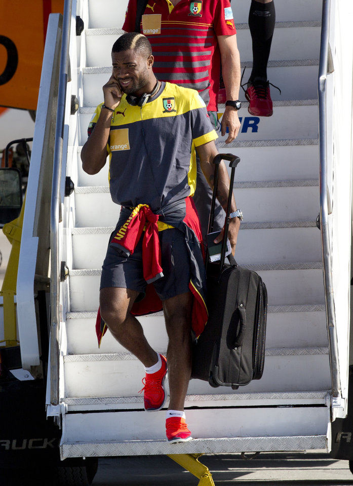 Photo - FC Barcelona's player Alex Song descends the stairs of the aircraft  as Cameroon's national team arrives at the Galeao Air Base in Rio de Janeiro, Brazil, Monday, June 9, 2014. Cameroon's World Cup team refused to board a plane due to take them to Brazil on Sunday because of a long-running dispute over bonus payments for the tournament, forcing their national federation to take out a loan to meet their demands. (AP Photo/Rodrigo Abd)