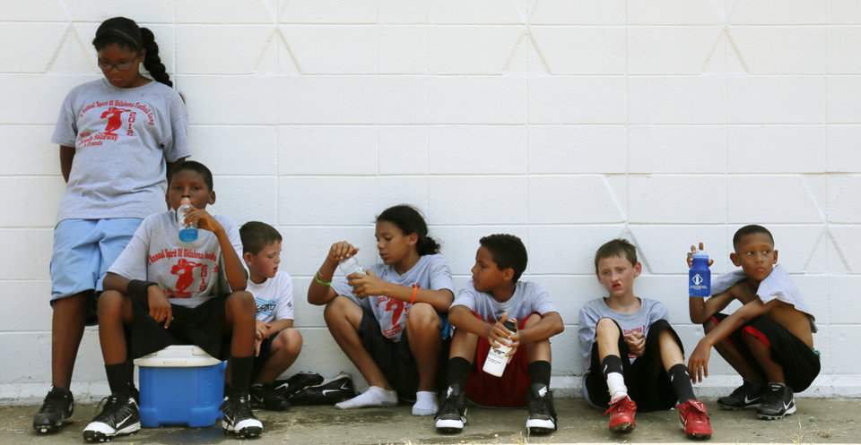 Photo - Children take a break during former OU quarterback Jamelle Holieway's Spirit of Oklahoma football camp in Weleetka, Okla., Friday, July 6, 2012. Photo by Nate Billings, The Oklahoman