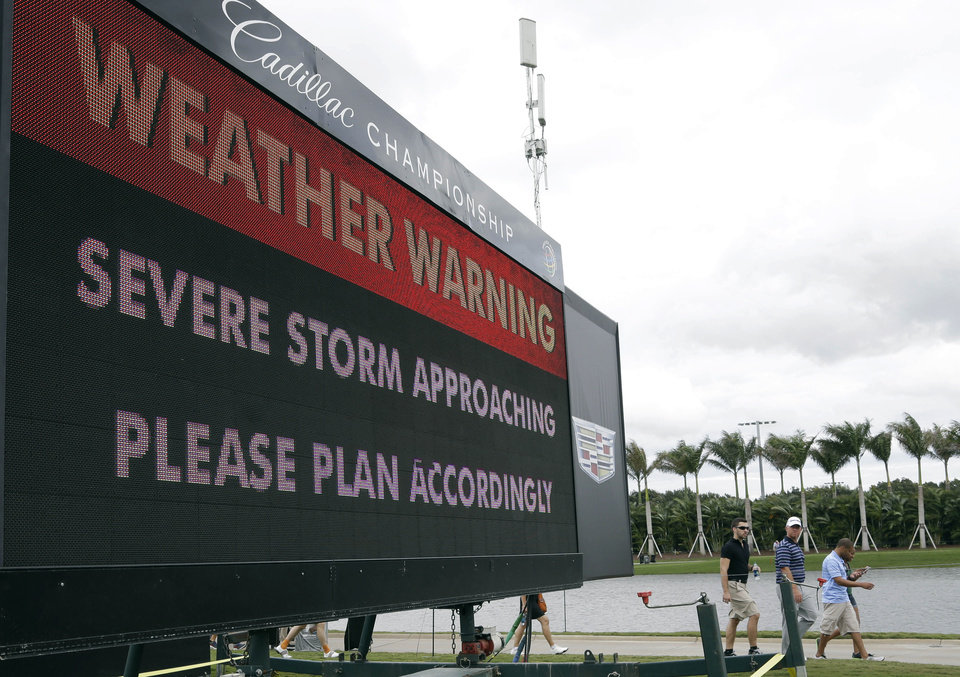 Photo - Spectators leave the golf course after play was suspended due to approaching inclement weather during the first round of the Cadillac Championship golf tournament, Thursday, March 6, 2014, in Doral, Fla. (AP Photo/Lynne Sladky)