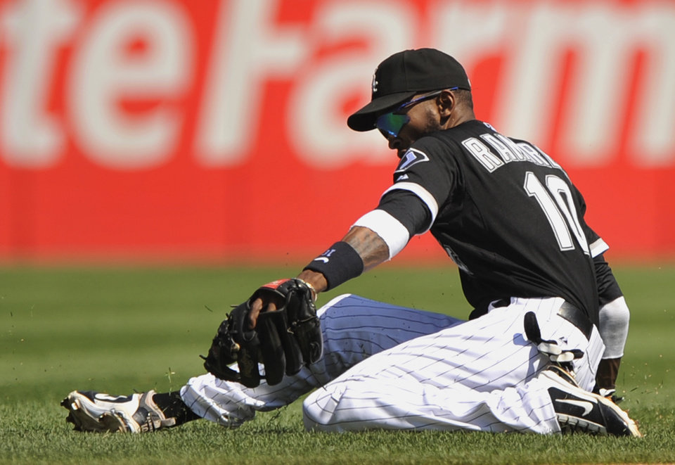 Photo - Chicago White Sox shortstop Alexei Ramirez stops a grounder hit by Atlanta Braves' Chris Johnson before throwing him out at first base during the first inning of an interleague baseball game in Chicago, Saturday, July 20, 2013. (AP Photo/Paul Beaty)