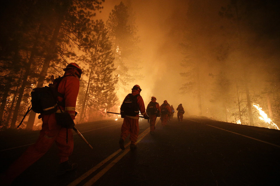 Photo - Inmate firefighters walk along state Highway 120 as firefighters continue to battle the Rim Fire near Yosemite National Park, Calif., on Sunday, Aug. 25, 2013. Fire crews are clearing brush and setting sprinklers to protect two groves of giant sequoias as a massive week-old wildfire rages along the remote northwest edge of Yosemite National Park. (AP Photo/Jae C. Hong)