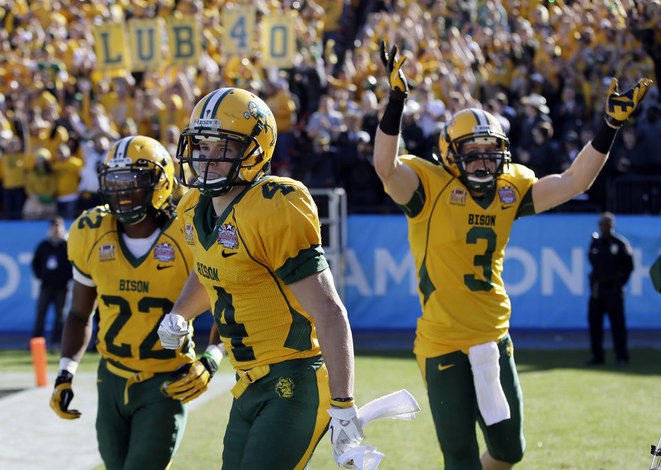 Photo - North Dakota State's Sam Ojuri, left, Ryan Smith (4), and Trevor Gebhart (3) celebrate a touchdown by Smith in the first half of the FCS championship NCAA college football game against Towson, Saturday, Jan. 4, 2014, in Frisco, Texas. (AP Photo/Tony Gutierrez)