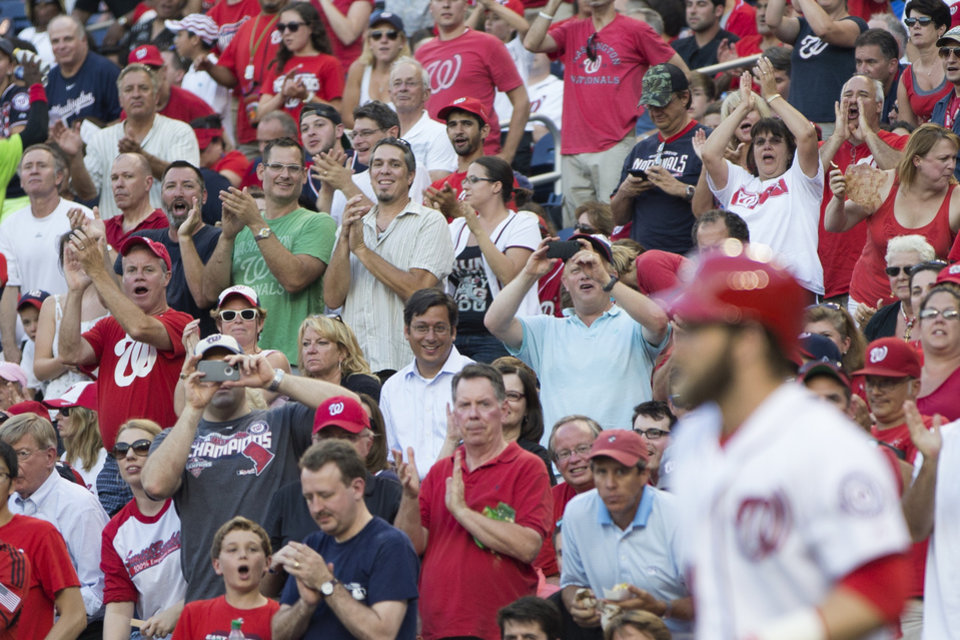 Photo - Fans stand for Washington Nationals left fielder Bryce Harper as he walks out for his first at bat since returning from the disabled list during the second inning of a baseball game against the Colorado Rockies at Nationals Park, on Monday, June 30, 2014, in Washington. Harper, who missed 57 games because of a torn ligament in his left thumb, was batting sixth and playing left field as the Nationals opened a series against the Colorado Rockies on Bryce Harper bobblehead night. (AP Photo/ Evan Vucci)