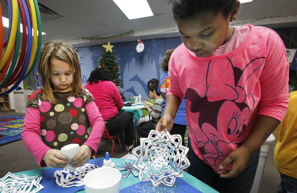 Emma Vadnais, 6, and Aushae Farris, 8, make snowflakes to send to the students at Sandy Hook Elementary School to brighten their classrooms. Photo By David McDaniel, The Oklahoman