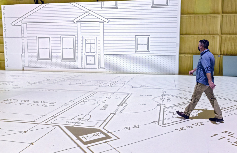 Photo -  Projected Plans owner and founder Brian Porch walks  a life-size blueprint. [CHRIS LANDSBERGER/THE OKLAHOMAN]
