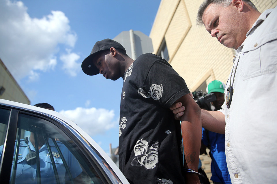 Photo - Shawn Scott, who with his younger brother Akien is accused of the Mother's Day second-line shooting which injured 20 people, is taken from the 5th District Police Station to Orleans Parish Prison in New Orleans on Thursday, May 16, 2013. (AP Photo/The Times-Picayune, Michael DeMocker)