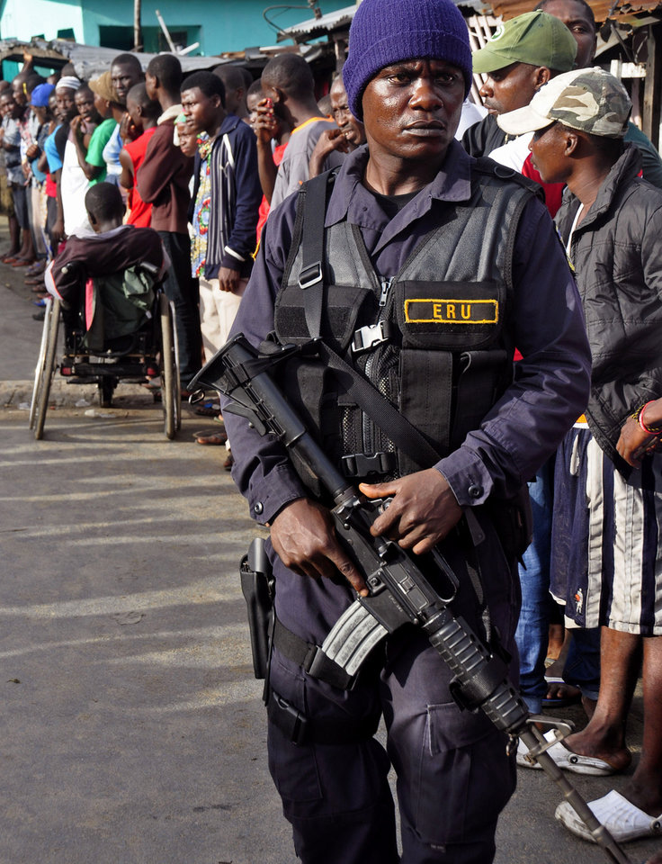 Photo - A Liberian security officer patrols in the West Point area, as the government clamps down on the movement of people to prevent the spread of the Ebola virus in Monrovia, Liberia, Wednesday, Aug. 20, 2014. Security forces deployed Wednesday to enforce a quarantine around a slum in the Liberian capital, stepping up the government's fight to stop the spread of Ebola and unnerving residents. (AP Photo/Abbas Dulleh)