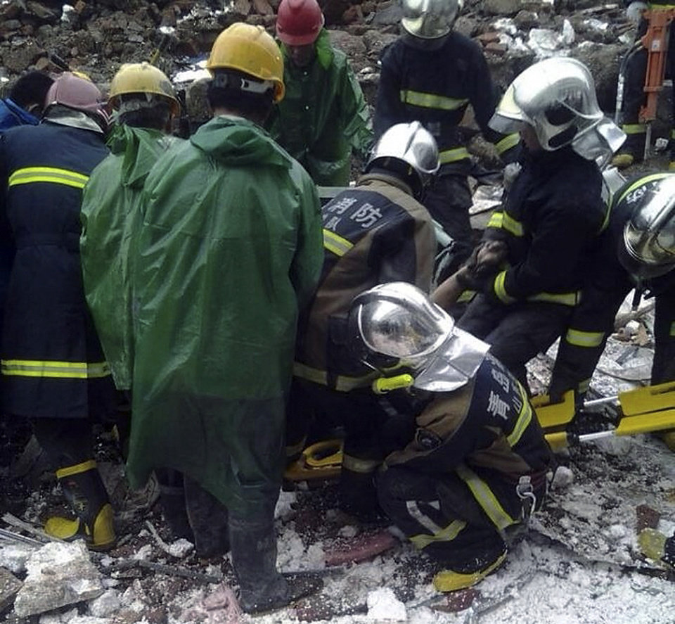 Photo - In this photo taken by mobile phone, firefighters pull out a victim following a wall collapse in Qingdao in east China's Shandong province Sunday, May 11, 2014. The wall collapse triggered by heavy rains at a recycling plant killed 18 people and injured three others early Sunday in the eastern city of Qingdao, state media reported. (AP Photo) CHINA OUT