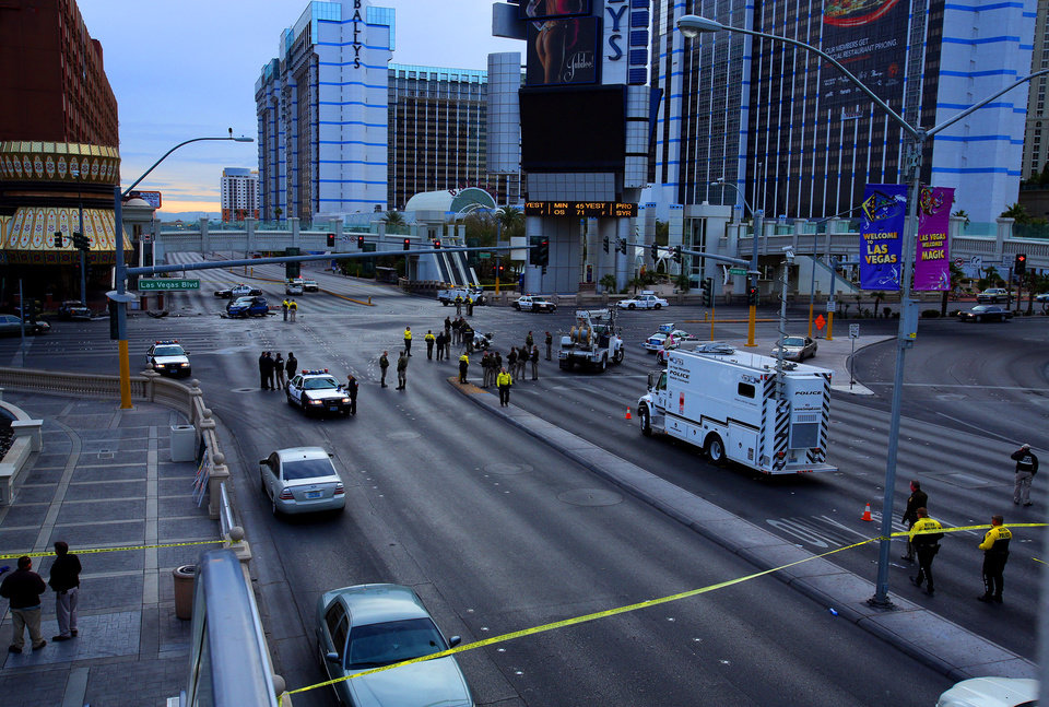 Law enforcement personal investigate the scene of a mulit-vehicle accident on Las Vegas Blvd. and Flamingo Road Thursday, Feb. 21, 2013. Authorities say a Range Rover opened fire on a Maserati at a stoplight, sending it crashing into a taxi that went up in flames, leaving three people dead and at least six injured. Police were checking with nearby businesses to see whether a previous altercation prompted the car-to-car attack  (AP Photo/Las Vegas Review-Journal, Jeff Scheid) LOCAL TV OUT; LOCAL INTERNET OUT; LAS VEGAS SUN OUT