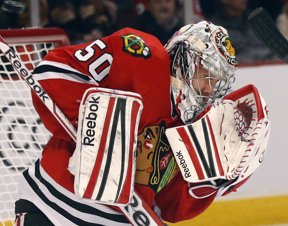 Photo - Chicago Blackhawks goalie Corey Crawford makes a save and deflects the puck into the safety net above the ice during the first period of an NHL hockey  game against the Los Angeles Kings, Monday, March 25, 2013, in Chicago. (AP Photo/Charles Rex Arbogast)