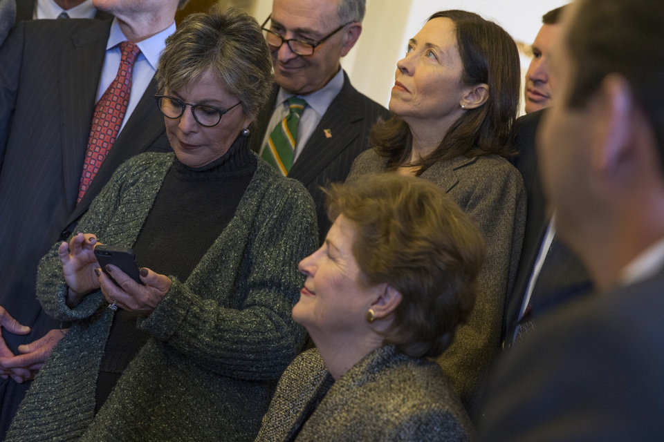 Photo - Senate Environment and Public Works Committee Chairman Sen. Barbara Boxer, D-Calif., left, checks her phone during a meeting of the Senate Climate Action Task Force prior to taking to the Senate Floor all night to urge action on climate change on Monday, March 10, 2014, in Washington. From left, Boxer, Sen. Chuck Schumer, D-N.Y., Sen. Jeanne Shaheen, D-N.H., and Sen. Maria Cantwell, D-Wash. (AP Photo/ Evan Vucci)