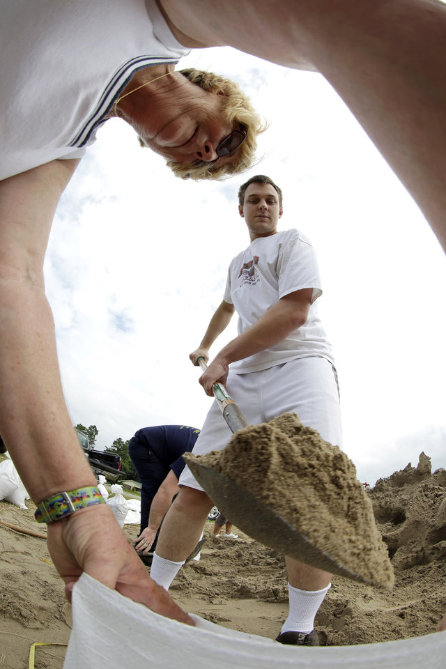 Photo -   Richard Sackfield, center, fills a sandbag for Annie Savoie, left, as Isaac nears landfall Tuesday, Aug. 28, 2012, in Houma, La. Isaac is churning it's way across the Gulf of Mexico heading towards Louisiana. (AP Photo/David J. Phillip)