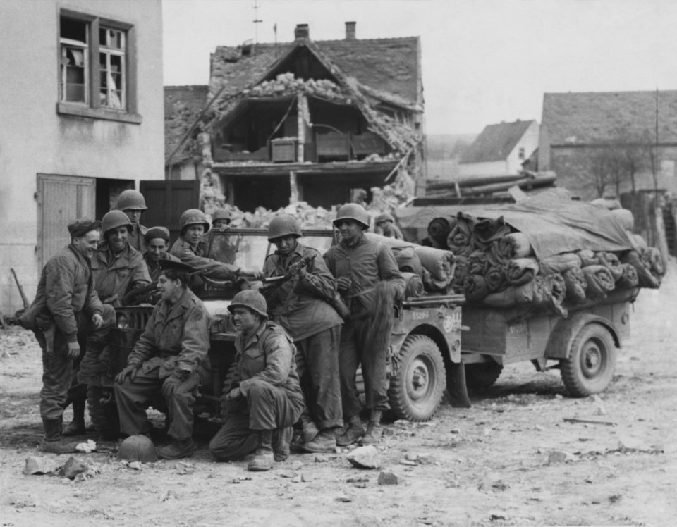 Photo - These members of the 180th infantry regiment wait for orders to move up after occupying a ruined village in Germany on their push to Neurenberg and thence down to Munich.  It was at Munich that the war ended for the Thunderbird division, which wrote a bright chapter of combat achievement. This was a ruined town in Germany as these 180th infantrymen paused on the road to Nurnberg and war's end at Munich.  Those Nazi shrine cities fell to the 45th.  In the great arena where Hitler roused his rabble, the 45th stood at attention as Maj. Gen. Robert Fredericks led a memorial to the division's honored dead.;  Photographer unknown and photo undated.  Published in The Daily Oklahoman on 08/13/1950 and 11/01/1953.