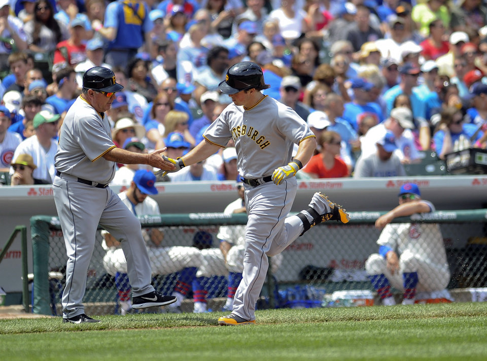 Photo - Pittsburgh Pirates right fielder Travis Snider, right, high-fives third base coach Nick Leyva after he homers in the third inning of a baseball game against the Chicago Cubs, Sunday, June 22, 2014, in Chicago. (AP Photo/Matt Marton)