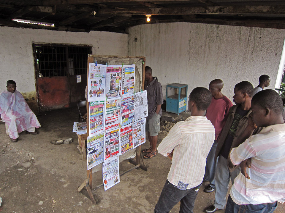 Photo - People read local newspaper headlines focusing on the Ebola outbreak, including a newspaper, left,  reading 'Burn all bodies' in the city of Monrovia, Liberia, Thursday, July 31, 2014. The worst recorded Ebola outbreak in history surpassed 700 deaths in West Africa as the World Health Organization on Thursday announced dozens of new fatalities. (AP Photo/Jonathan Paye-Layleh)