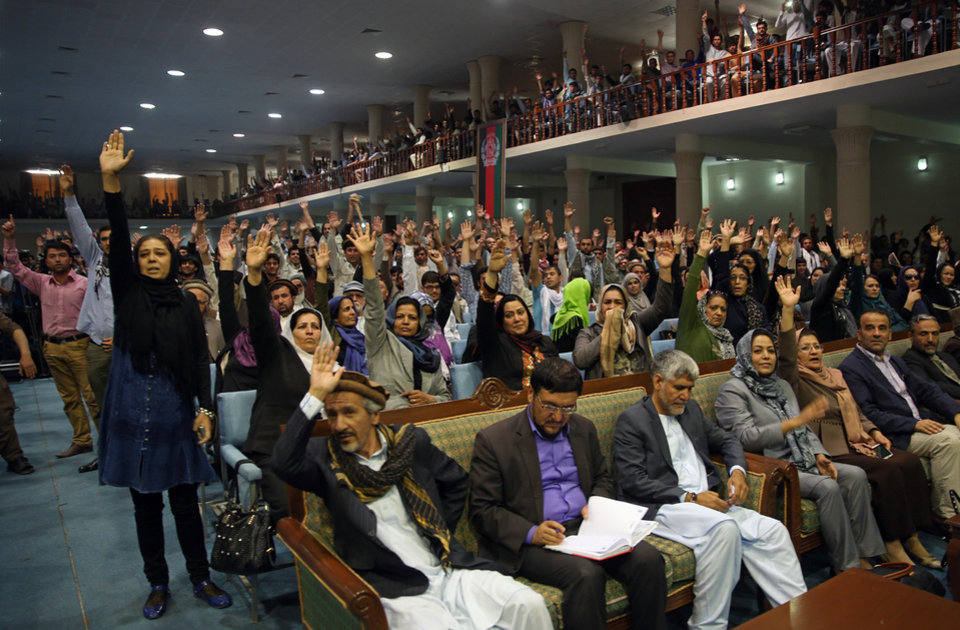 Photo - Supporters of Afghan presidential candidate Abdullah Abdullah raise their hands in support during his speech at a gathering in Kabul, Afghanistan, Tuesday, July 8, 2014. Abdullah says he received calls from President Barack Obama and U.S. Secretary of State John Kerry after he refused to accept the preliminary result of the vote citing fraud. Abdullah  told his supporters the results of the election were fraudulent but asked them to give him a few more days to negotiate. (AP Photo/Massoud Hossaini)