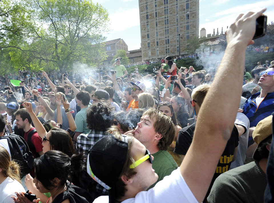 Photo -   A crowd of marijuana supporters light up at 4:20 p.m. outside the Duane Physics building during the 4/20 rally on the University of Colorado campus in Boulder, Colo., on Friday, April 20, 2012. Many students at the University of Colorado and other campuses across the country have long observed 4/20. The counterculture observation is shared by marijuana users from San Francisco's Golden Gate Park to New York's Greenwich Village. (AP Photo/The Daily Camera, Jeremy Papasso)