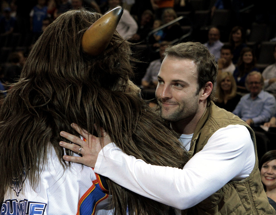 Photo - Pro football payer and Oklahoma City native Wes Welker gets a hug from Thunder mascot Rumble during a time out as the Oklahoma City Thunder defeat the Portland Trail Blazers 106-92 in NBA basketball at the Chesapeake Energy Arena in Oklahoma City, on Friday, Nov. 2, 2012.  Photo by Steve Sisney, The Oklahoman