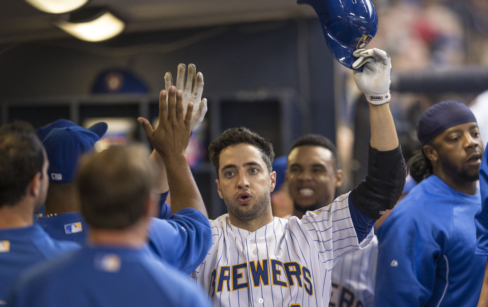 Photo - Milwaukee Brewers' Ryan Braun is greeted by teammates after scoring against the Pittsburgh Pirates during the fourth inning of a baseball game on Sunday, April 13, 2014, in Milwaukee. (AP Photo/Tom Lynn)
