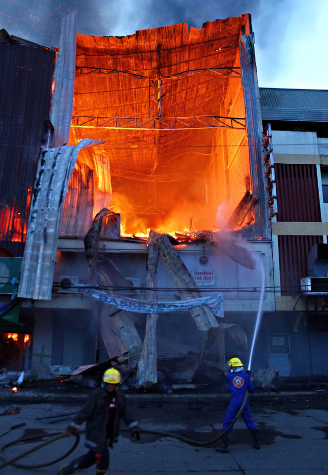 Photo -   Firefighters battle the blaze in an early morning fire Wednesday, May 9, 2012 in Butuan City in Mindana island, southern Philippines. The inferno at the three-storey clothing store killed at least 17 employees, most of whom were women who were asleep and trapped on the top floor, officials said. (AP Photo/Erwin Mascarinas)