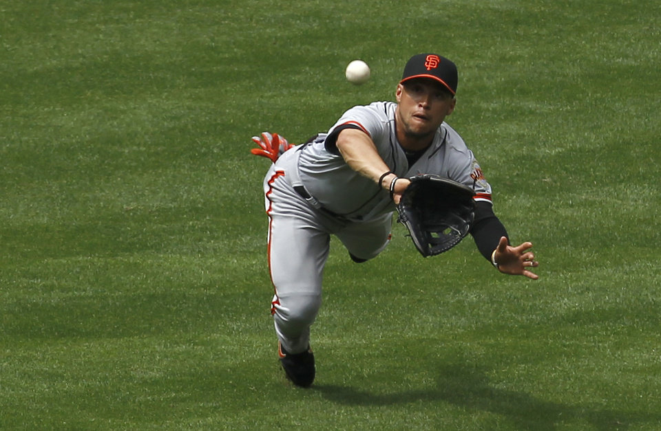 Photo -   San Francisco Giants' Gregor Blanco makes a diving catch on a line drive by Arizona Diamondbacks' Ryan Roberts during the fourth inning in an MLB baseball game Sunday, April 8, 2012, in Phoenix.(AP Photo/Ross D. Franklin)