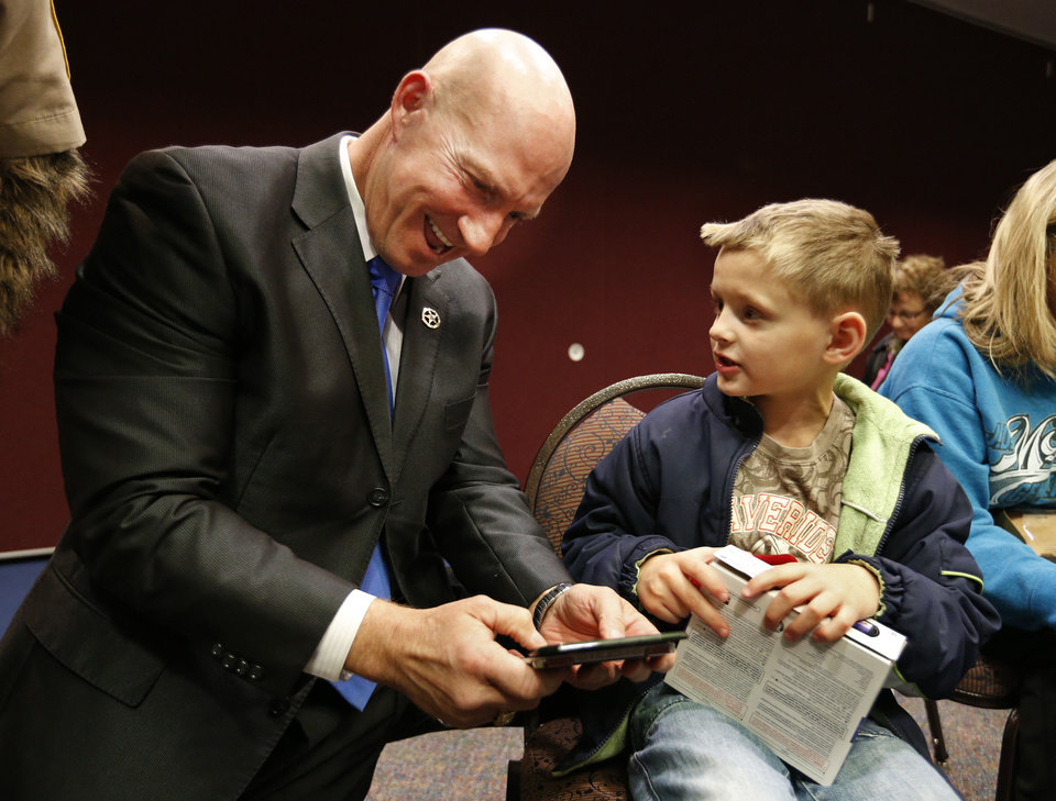Darrell Weaver, director of the Oklahoma Bureau of Narcotics and Dangerous Drugs, gives an electronic gaming system to Max, 6, at the J.D. McCarty Center in Norman. PHOTO BY STEVE SISNEY, THE OKLAHOMAN