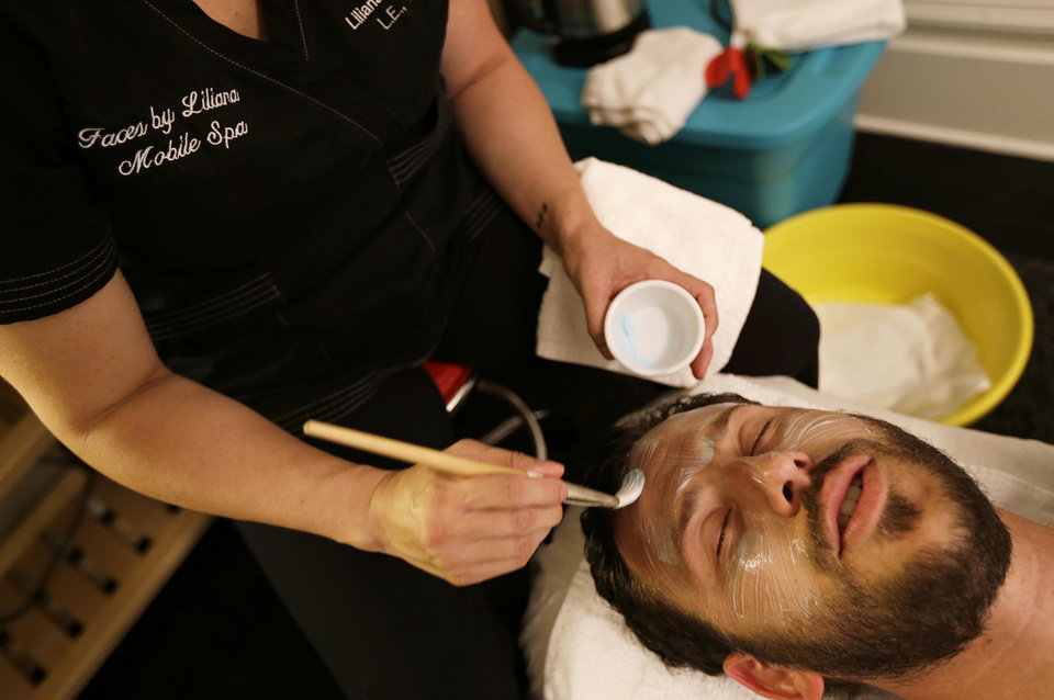 Photo - In this photo taken Tuesday, July 29, 2014, Liliana Aranda, owner of Faces By Liliana, applies a molecular rice mask to Dr. Austin Davis at his chiropractic office in San Francisco. Aranda's four-year-old company gives facials, massages and other spa treatments in homes or offices in the San Francisco area. (AP Photo/Eric Risberg)