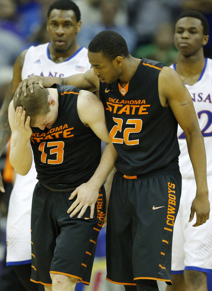 Photo - Oklahoma State guard Phil Forte, III (13) is helped by Oklahoma State guard Markel Brown (22) after hitting his head while fouling Kansas guard Andrew Wiggins during overtime of an NCAA college basketball game in the quarterfinals of the Big 12 Conference men's tournament in Kansas City, Mo., Thursday, March 13, 2014. Kansas defeated Oklahoma State 77-70 in overtime. (AP Photo/Orlin Wagner)