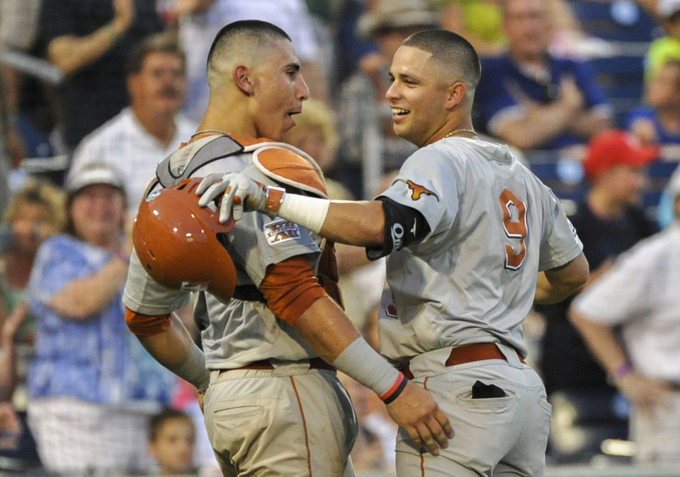 Photo - Texas' C.J Hinojosa (9) celebrates with Texas catcher Tres Barrera (1) after Hinojosa hit a solo home run in the seventh inning of an NCAA baseball College World Series elimination game against UC Irvine in Omaha, Neb., Wednesday, June 18, 2014. (AP Photo/Ted Kirk)