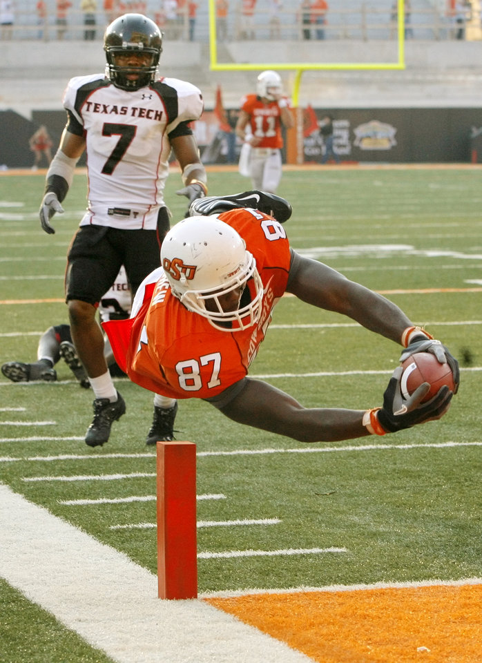 Photo - OSU's Brandon Pettigrew (87) dives into the end zone for a touchdown in front of Texas Tech's Darcel McBath (7) in the fourth quarter of the college football game between the Oklahoma State University Cowboys (OSU) and the Texas Tech University Red Raiders (TTU) at Boone Pickens Stadium in Stillwater, Okla., on Saturday, Sept. 22, 2007. OSU won, 49-45. Pettigrew's touchdown was the go-ahead score for the Cowboys. By NATE BILLINGS, The Oklahoman