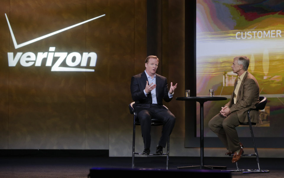 Photo - FILE - In this Jan. 8, 2013, file photo, NFL football commissioner Roger Goodell, left, and Verizon CEO Lowell McAdam talk about Verizon mobile products that allow NFL fans to watch games and interact with each other at the Consumer Electronics Show, in Las Vegas. The parent of the country's biggest wireless carrier lost $4.23 billion, or $1.48 per share, for the period ended Dec. 31. That compares with a loss of $2.02 billion or 71 cents per share, a year ago. (AP Photo/Julie Jacobson)