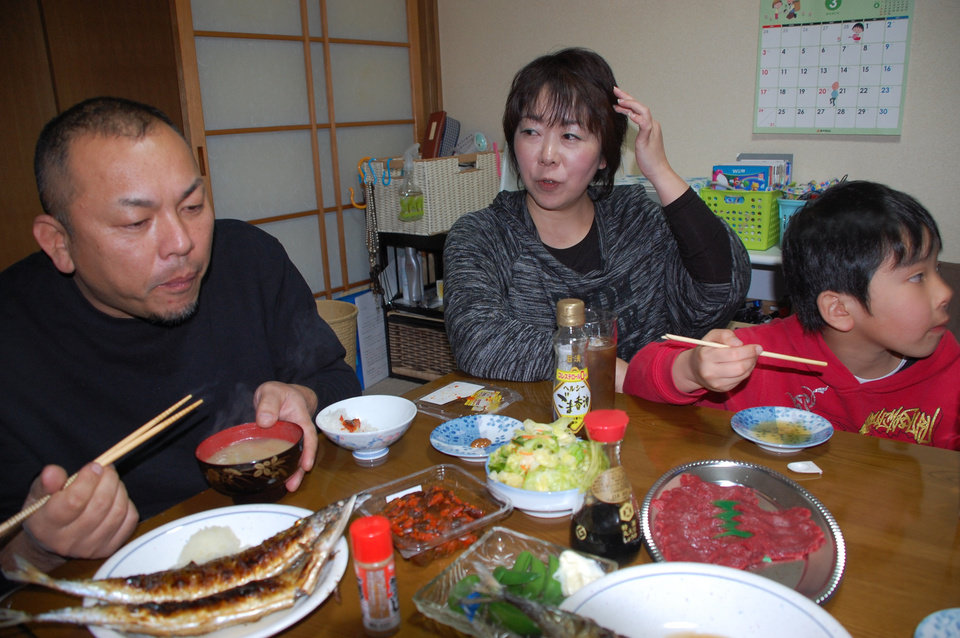 In this Friday, March 1, 2013 photo, truck driver Takahiro Ishitani, accompanied by his wife, Yuko, eats dinner with his son, Ryusei at a rented house his family has evacuated to in Iide, Yamagata prefecture, Japan. During the week, Ishitani lives and works as truck driver in Minami-Soma, near the Fukushima Dai-ichi nuclear power plant, but the rest of his family has moved away to shield the children from the possible radiation risk. Every weekend, he drives three hours into the mountains to visit them, wondering if the family will ever return to his hometown. (AP Photo/Malcolm Foster)