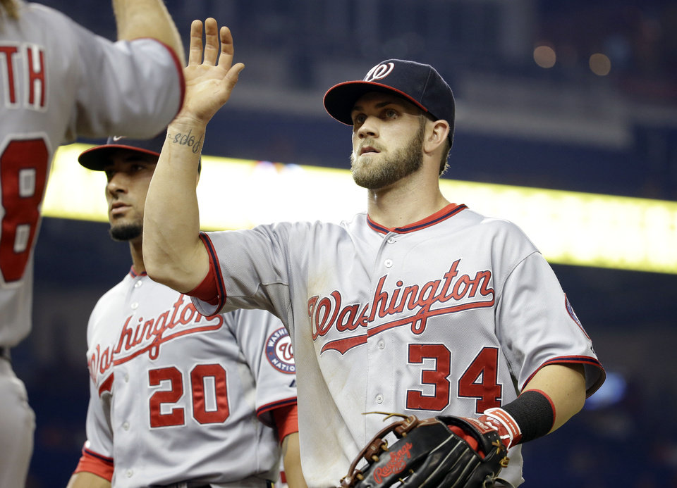Photo - Washington Nationals' Bryce Harper (34) is congratulated by Jayson Werth, left, after throwing to the infield to get Miami Marlins' Jarrod Saltalamacchia out at second to end the fifth inning during a baseball game, Monday, July 28, 2014, in Miami. (AP Photo/Lynne Sladky)
